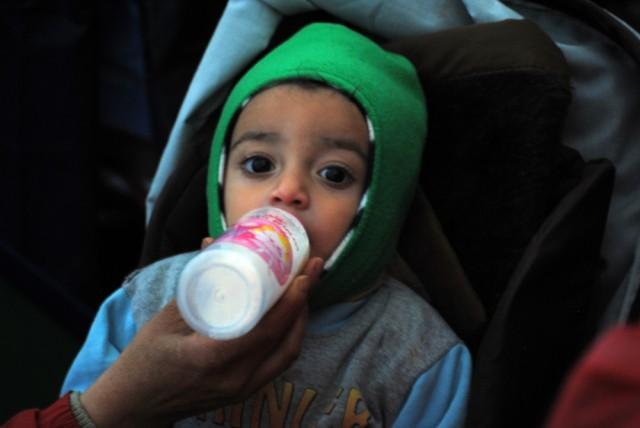 Jinda da el biberón, que calienta entre sus manos, al pequeño Yahya de 18 meses. / B. R.